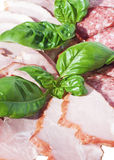 Cutting sausage and cured meat with a basil Stock Image