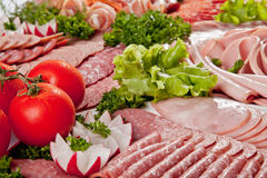 Cutting sausage and cured meat with a parsley Royalty Free Stock Photos