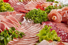 Cutting sausage and cured meat with a parsley Royalty Free Stock Photography