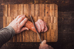 Cutting sausage on the wooden board Royalty Free Stock Photo