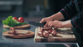 Cutting the sausages on a cutting board. In the kitchen of restaurant stock video