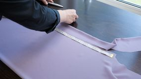 Seamstress makes pattern from cloth to sew clothes, measures with tape on table. stock footage