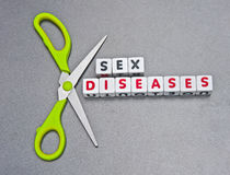 Cutting sex diseases. Pair of scissors with green handles set against text  sex diseases  in uppercase letters inscribed on small white cubes, gray background Royalty Free Stock Image