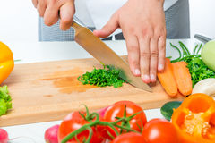 Cutting with a sharp knife parsley close up. On a wooden board Royalty Free Stock Image