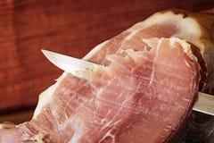 Cutting a slice of Spanish ham. Horizontally. Royalty Free Stock Photos