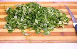 Cutting sorrel by knife on the wooden cooking desk. In the kitchen stock photos