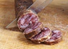Cutting spanish salami slices Stock Photo