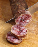 Cutting spanish salami slices with a knife Stock Images