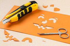 Cutting a stencil of paper for jack-o'-lantern Stock Images