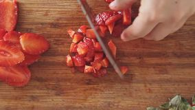 Cutting strawberry on cutting board. Woman cutting strawberry with big kitchen knife on wooden cutting board video footage filmed in slow motion from above stock video