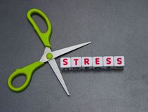 Cutting stress. Pair of green handled scissors against text Stock Photos