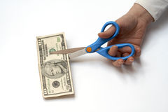 Cutting a ten dollars with scissors Stock Photos