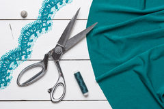 Cutting textile or fine cloth with a tailor scissors on wooden t Stock Photos