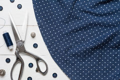Cutting textile or fine cloth with a taylor scissors on wooden t Royalty Free Stock Photo