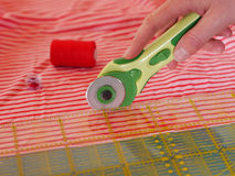 Cutting textiles. Close up of cutting fabric with rotary cutter Royalty Free Stock Photo