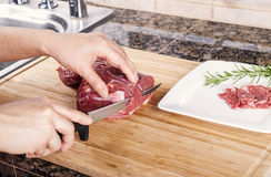 Cutting Thin Slices of Lean Red Lamb Meat Stock Photo