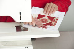 Cutting thread from fabric. A quilter cuts off thread from a paper pieced foundation quilt block Royalty Free Stock Image
