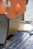 Cutting tiles machine. A close-up of a mechanical rotary saw, cutting a ceramic tile Stock Photo