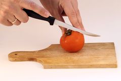 Cutting a tomato. Isolated Stock Image