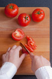 Cutting tomato on board Royalty Free Stock Photos