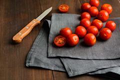 Cutting tomato cherry and some tomatoes on wooden background. Cutting tomato cherry and some tomatoes with knife on wooden background stock image