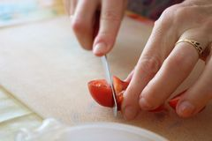 Cutting tomato slice on cutting board, woman hands close up Royalty Free Stock Images