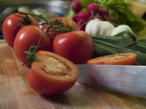 Cutting Tomatoes. At kitchean board, vegetables at background stock photo