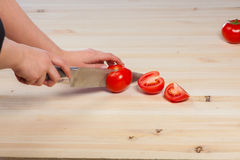 Cutting tomatoes for dishes on the table. Vegetables during the cooking process dishes. Vegetables for healthy eating Royalty Free Stock Image