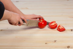 Cutting tomatoes for dishes on the table. Vegetables during the cooking process dishes. Vegetables for healthy eating Stock Photos
