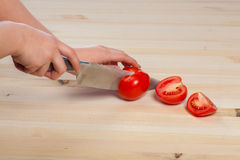 Cutting tomatoes for dishes on the table. Vegetables during the cooking process dishes. Vegetables for healthy eating Royalty Free Stock Photos