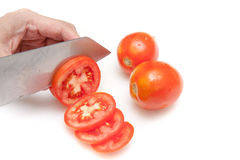 Cutting tomatoes into small slices on white background isolated Stock Photography
