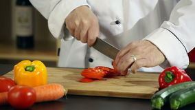 Cutting tomatoes. Video of a chef chopping tomatoes on a wooden cutting board in a restaurant kitchen stock footage