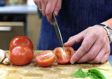 Cutting tomatos. Hands  of the chef cutting tomatos Royalty Free Stock Image
