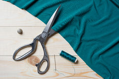 Cutting turquoise fabric with a taylor scissors on wooden table Royalty Free Stock Image