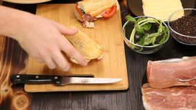 Cutting two sandwiches in two at the kitchen. On wooden board stock video