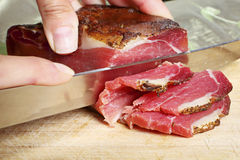 Cutting Tyrollean Bacon. Close up af some hands cutting a tyrollean bacon royalty free stock photos