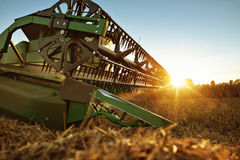 Cutting unit of a combine harvester at sunset Royalty Free Stock Photo