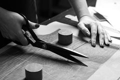 Cutting up the fabric with tailor scissors for further bespoke exclusive fashioning. Tailor atelier - handmade exclusive clothes making and repair, private stock photography