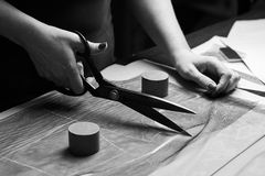 Cutting up the fabric with tailor scissors for further bespoke exclusive fashioning. Tailor atelier - handmade exclusive clothes making and repair, private stock images