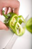 Cutting vegetables. Cutting a green pepper on slices with a knife Royalty Free Stock Images