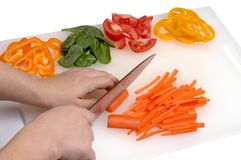 Cutting Vegetables. Closeup of a cook's hands chopping fresh veggies royalty free stock photos