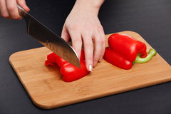 Cutting the vegetables with a kitchen knife on the board Royalty Free Stock Photography