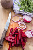 Cutting vegetables on wooden board. Cutting beetroot, onions, arugula with a knife on wooden board Stock Photography