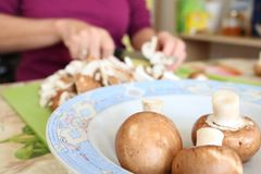 Cutting washed button mushrooms close up. Woman preparing lunch cutting portobello button mushrooms for cooking in a kitchen using cutting board and knife. Focus Stock Photos