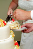 Cutting The Wedding Cake. Hands of a bride and groom holding a knife and cutting into their wedding cake Royalty Free Stock Photos