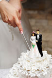 Cutting the wedding cake. With figurines of the bride and groom Stock Images