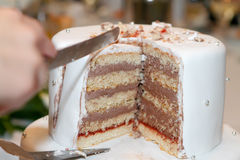 Cutting the Wedding Cake. Hands holding a knife and cutting wedding cake Royalty Free Stock Photos