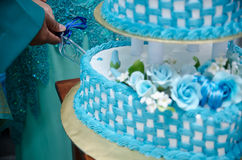 Cutting Wedding Cake. Closeup view of a three layered wedding cake being cut by the groom and bride Royalty Free Stock Photo