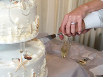 Cutting a wedding cake. A bride and groom join hands to cut their wedding cake Royalty Free Stock Photos