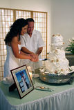 Cutting the Wedding Cake. A newly married couple happily cuts their wedding cake Stock Photography